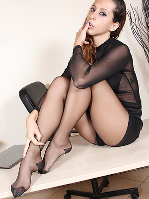 Beautiful brunette in sexy black nylon pantyhose shows her perfect feet and soles