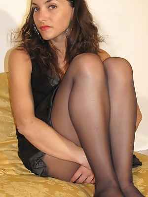 Beautiful brunette in black pantyhose entertain herself with her perfect feet
