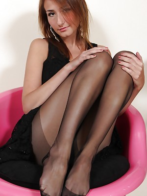 Hot brunette in black pantyhose shows her feet and soles
