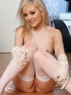 Faye in white lace dress and gloves, white fishnet stockings and 4 inch heels teases as she slowly reveals her body before pulling down her panties and fingering herself in her lace gloves