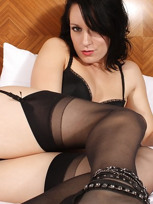 Jasmine strips to her stockings on the bed to play with her toy