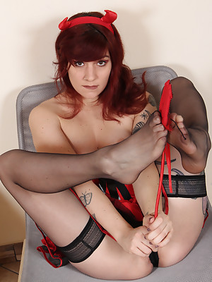 Gorgeous redhead dressed as devil girl shows her perfect soft soles in black stockings