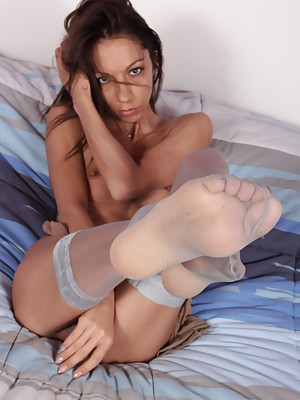 Hot brunette shows her feet in sheer pantyhose