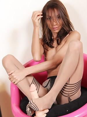 Hot brunette wraps a dildo between her hosed feet
