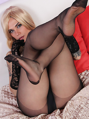 Gorgeous blonde babe shows her boobs and her sexy feet in nylons